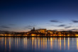 The lights of the city of Hondarribia are reflected in the sea water at night, Euskadi