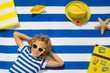 Top view portrait of child on striped beach towel