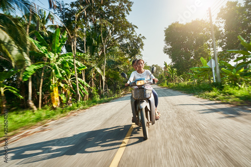 thai mother and daughter riding motorbike through rural thailand