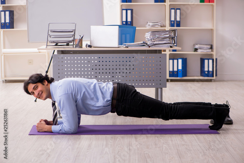 Leinwanddruck Bild Young handsome male employee doing exercises in the office