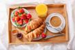 breakfast tray in bed : coffee, croissants, orange juice and fresh strawberries