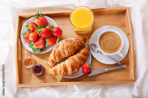 breakfast tray in bed : coffee, croissants, orange juice and fresh strawberries