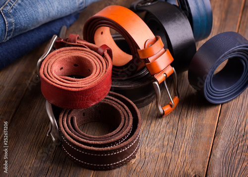 Leather colored belts on a wooden table. - 252651206