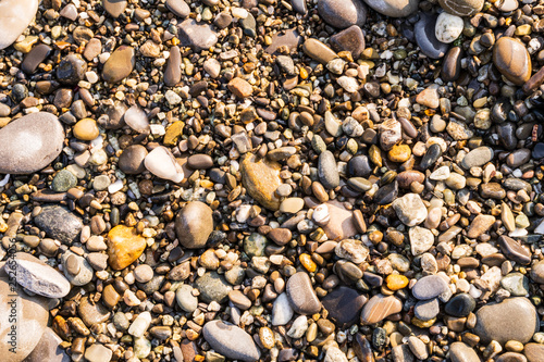 Flat lay of pebbles pattern on the sea shore.