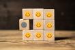 Leinwanddruck Bild - Viele Würfel mit lächelnden Smileys und einer der unzufrieden ist