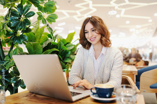 Beautiful businesswoman with toothy smile and brown hair dressed casual using laptop. Cafeteria interior. On desk coffee. - 252684617