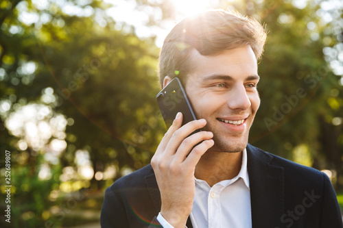 Close up of a smiling young business man walking
