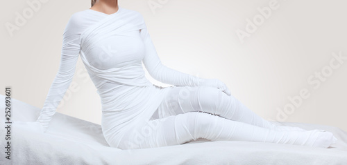 Leinwanddruck Bild The cosmetologist wraps the leg of the customer. Anti-cellulite procedure-STYX wrap.