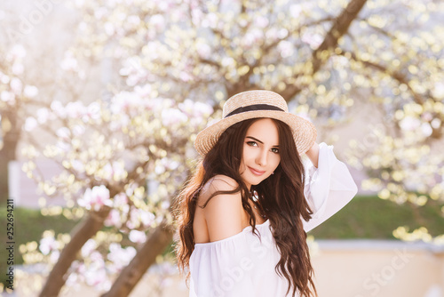 Leinwandbild Motiv Outdoor close up portrait of young beautiful happy smiling woman with long dark hair, makeup, wearing straw hat, white blouse, posing near blooming tree. Copy, empty space for text