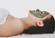 Leinwanddruck Bild - Side view of lying woman with green facial clay mask, white background.