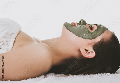 Leinwanddruck Bild Side view of lying woman with green facial clay mask, white background.