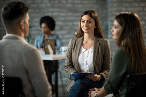 Happy insurance agent talking to her customers during a meeting in the office.
