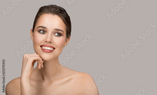 Portrait of young woman. Perfect clean skin and beautiful smile. Gray background.