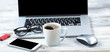 Cup of coffee with workstation technology in background