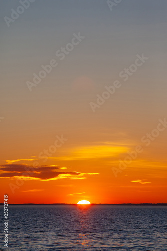 bright orange sun with reflection in the water during sunset over the sea - 252727419