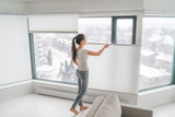 Woman opening home curtains in urban condo. Modern top down bottom up privacy cellular shades on apartment window keeping heat in winter with honeycomb blind curtain. Cordless pleated shades. - 252727829