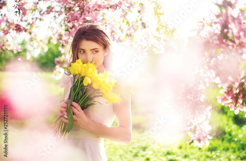 Beauty Portrait of Beautiful Young Brunette Woman In Nice Spring Dress With A Bouquet Of Tulips.Spring Style. Beautiful Spring Garden. Fashion Spring Summer Photo. Fashion and style concept. Long edge - 252728888