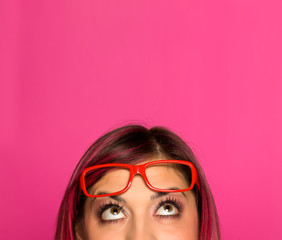 Half portrait of a young worried woman with pink hair and glasses on pink background © vladimirfloyd