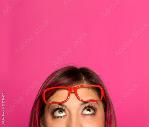 Half portrait of a young worried woman with pink hair and glasses on pink background