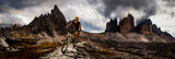 Cycling woman and man riding on bikes in Dolomites mountains andscape. Couple cycling MTB enduro trail track. Outdoor sport activity.