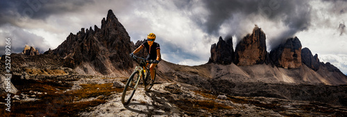 Leinwandbild Motiv Cycling woman and man riding on bikes in Dolomites mountains andscape. Couple cycling MTB enduro trail track. Outdoor sport activity.