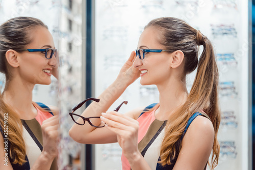 Young woman in optometrists store checking her looks in mirror - 252791052