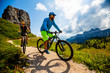 Leinwandbild Motiv Cycling woman and man riding on bikes in Dolomites mountains landscape. Couple cycling MTB enduro trail track. Outdoor sport activity.