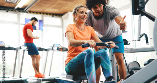 Personal trainer giving instructions a woman in gym buy photos
