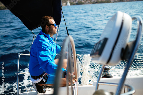 Handsome strong man sailing with his boat
