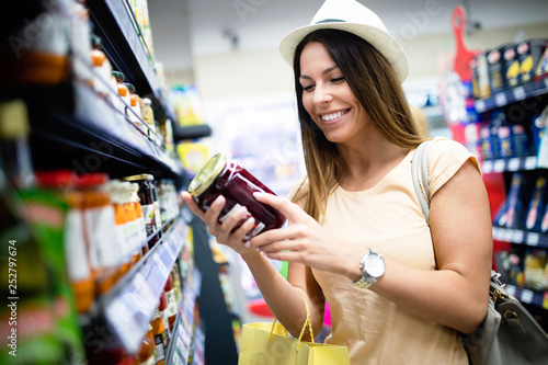 Smiling happy woman doing shopping in supermarket - 252797674