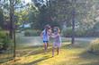 Leinwandbild Motiv Child playing with garden sprinkler. Kids run and jump. Summer outdoor water fun in the backyard