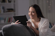 Happy woman watching media on tablet in the night - 252808837