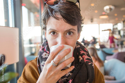 Portrait of a beautiful young woman in warm clothes sitting in cafe and drinkg coffee, blurred background, head and shoulders - 252815054