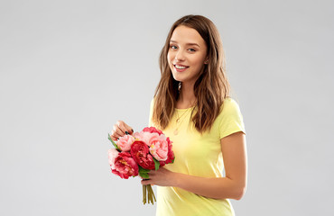 birthday and people concept - smiling young woman or teenage girl in yellow t-shirt with flower bouquet over grey background