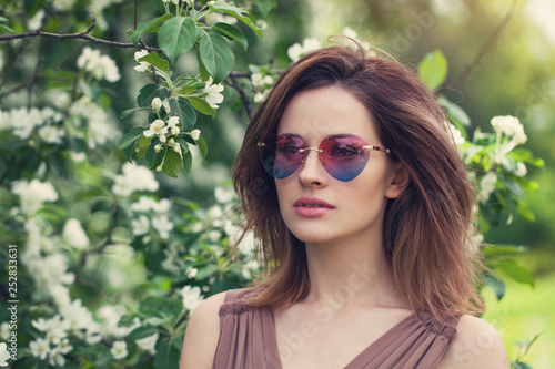 Young beautiful woman in sunglasses outdoors. Cute girl with brown layered hair,  spring portrait