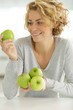smiling young woman holding apple