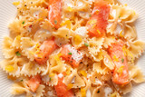 An overhead closeup photo of a plate of salmon pasta, Farfalle with smoked salmon and cream sauce, shot from the top