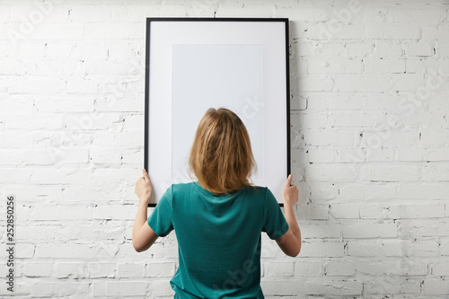 back view of woman holding mock up poster in frame