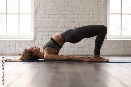 Leinwanddruck Bild Woman practicing yoga, Glute Bridge exercise, dvi pada pithasana pose