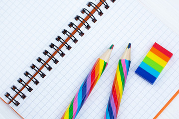 Open copybook with two rainbow-coloured pencils and a rubber on white wooden table