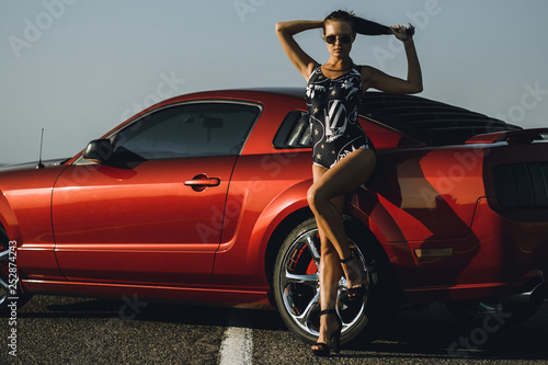 beautiful young woman with long dark hair in shorts sitting on the fender of red car on the sunset