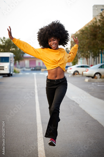 Young black woman with afro jumps, looking to camera, while crossing street, front view, vertical