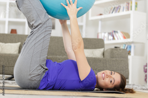 young woman training with fitness ball on grey background