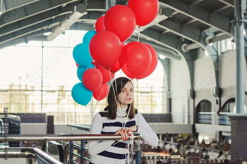 Young pretty woman holding red baloons in an indoor market hall