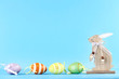 Wooden rabbit with easter eggs on blue background