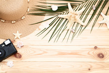 "Постер, картина, фотообои ""Seashells with palm leaf and retro camera on brown wooden table"""