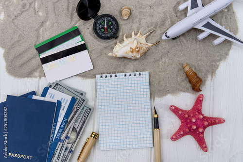 Leinwanddruck Bild Travelling plan with notepad and toy plane on sand