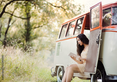 A young girl with a book by a car on a roadtrip through countryside, reading. © Halfpoint