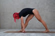 A girl with pink hair practices yoga.