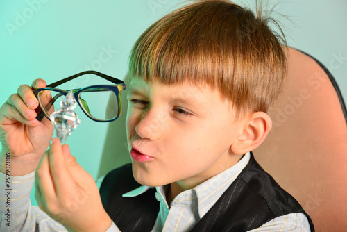 The child studies the gem through glasses, the concept of children, business, jewelry © andov